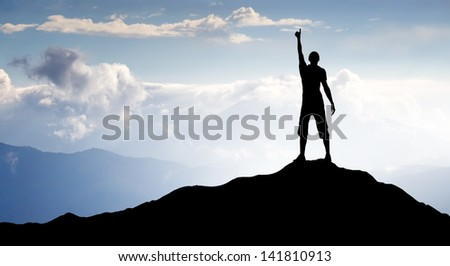 Silhouette of a winner on the mountain peak. Sport and active life