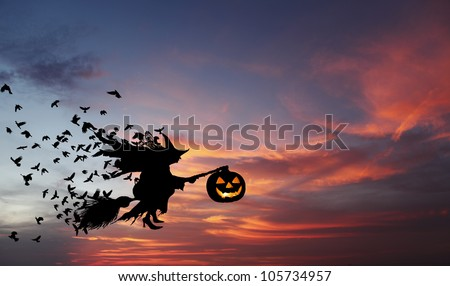 Silhouette of a witch flying on a broomstick carrying a sinister pumpkin lantern with flocks of crow following her during an eerie surreal evening, for Halloween concept.