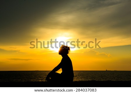 Silhouette of a woman against the sky at sunset