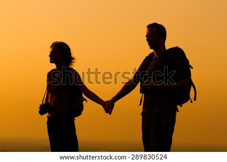 Silhouette of a woman and man with backpack looking at sunset.Couple with backpack watching the sunset - stock photo
