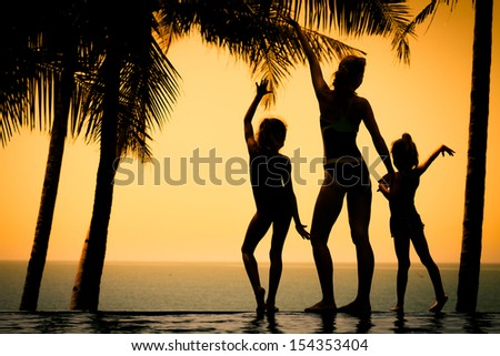 silhouette of a woman and two young girls standing by the pool on sea background