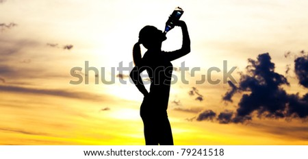 Silhouette of a  woman drinking water on the hill against yellow sky with clouds - stock photo