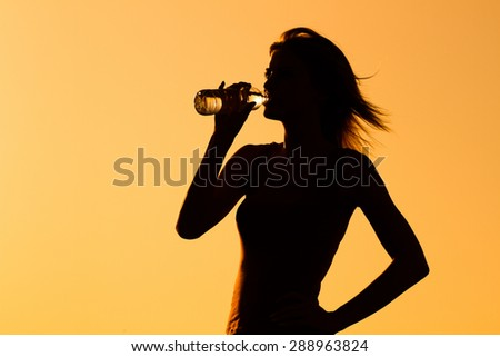 Silhouette of a woman drinking water.Refreshment - stock photo