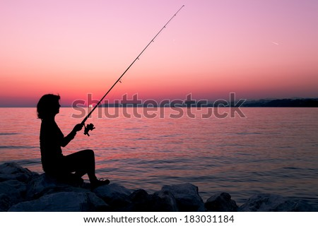 Silhouette of a woman, fishing on the coast and enjoying sunset sundown