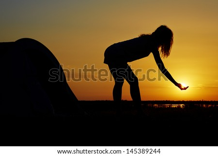Silhouette of a woman having fun near a camping tent at sunset.