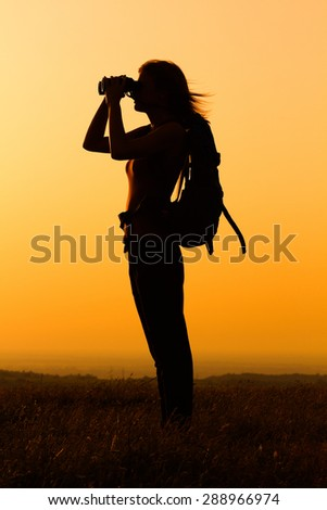Silhouette of a woman hiker watching sunset with binoculars.Woman hiker with binoculars - stock photo