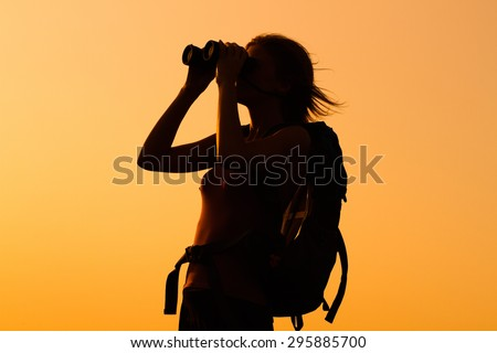 Silhouette of a woman hiker watching sunset with binoculars . Woman hiker with binoculars - stock photo