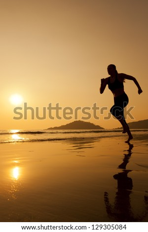Silhouette of a woman jogging on the beach - stock photo
