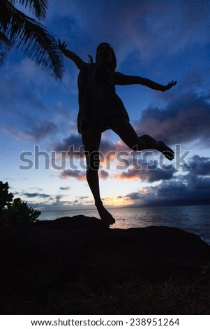 Silhouette of a woman jumping in the air in front of a sunset in hawaii
