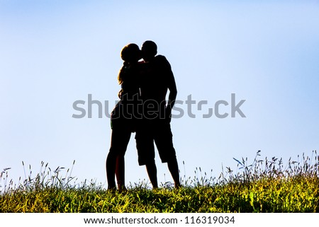 silhouette of a woman kissing a man on the sky background