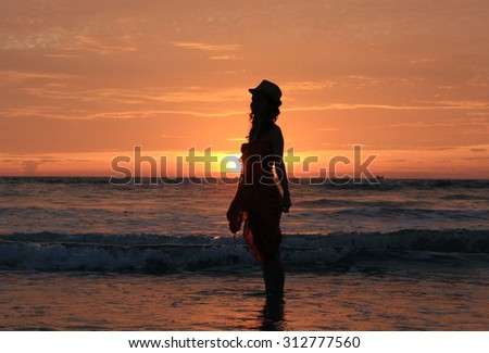 silhouette of a woman on a beach on background of beautiful picturesque colorful sunset with a view of the open Indian ocean with silhouette of ship on horizon - stock photo