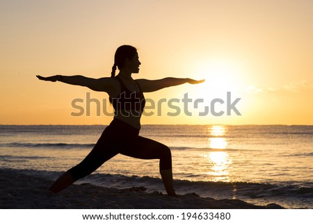 Silhouette of a woman practicing yoga by the beach at sunrise - stock photo