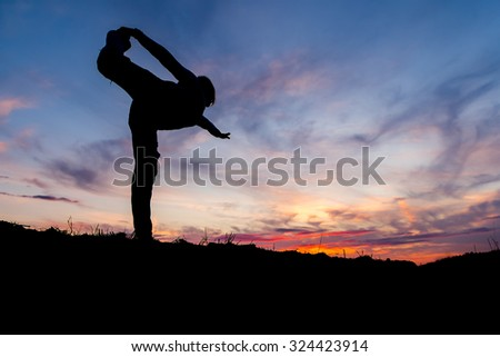 Silhouette of a woman practicing yoga during sunset - stock photo