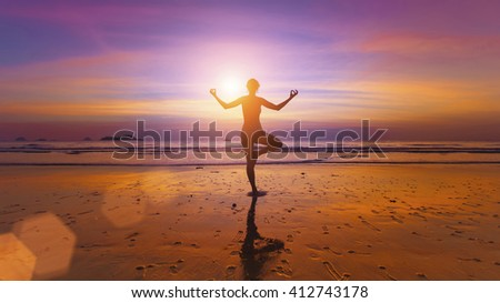 Silhouette of a woman practicing yoga on the ocean beach at amazing sunset. - stock photo