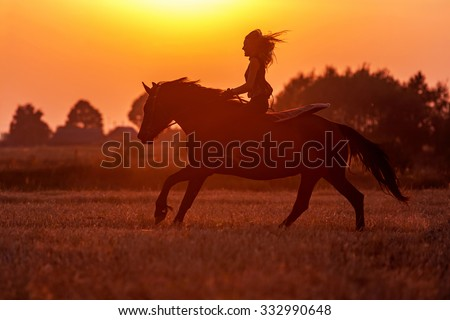 Silhouette of a woman riding a horse. - stock photo
