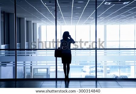 Silhouette of a woman standing alone against the backdrop of large windows office - stock photo