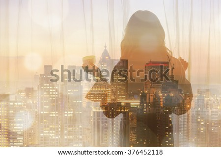 Silhouette of a woman standing in front of a window and holding a cup of coffee. - stock photo