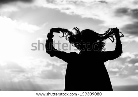 silhouette of a woman touching her hair in the air