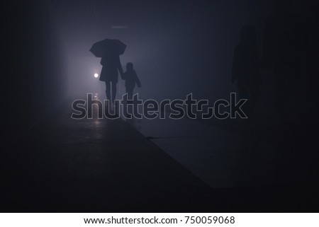 silhouette of a woman with a child walking under an umbrella in a tunnel