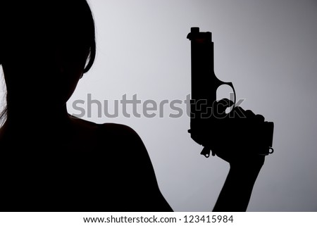 Silhouette of a woman with a gun on a gray background. - stock photo