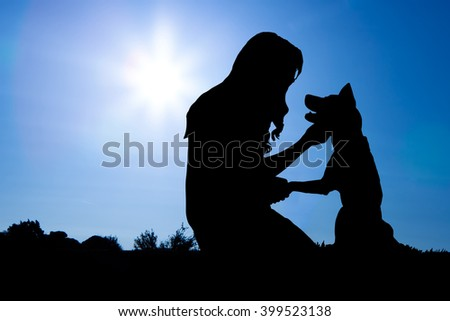 Silhouette of a woman with long hair sitting with a dog and shaking his hand