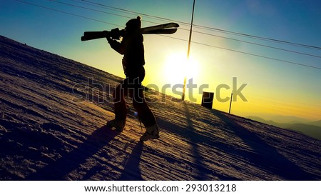 Silhouette of a woman with ski in winter mountains sunset close up - stock photo