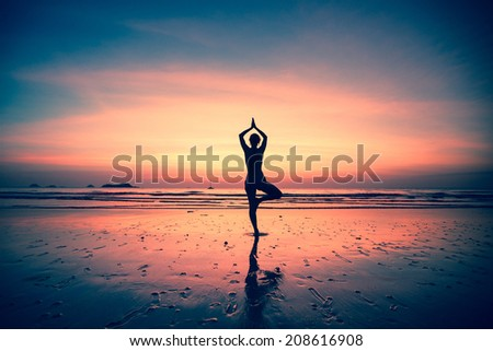 Silhouette of a woman yoga on sea coast at surreal sunset. - stock photo