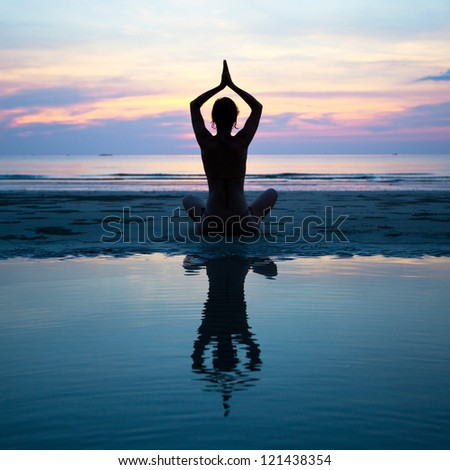Silhouette of a woman yoga on sea sunset with reflection in water - stock photo