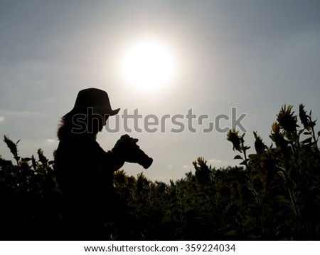 Silhouette of a women is looking a camera in sunflower farm under sunlight
