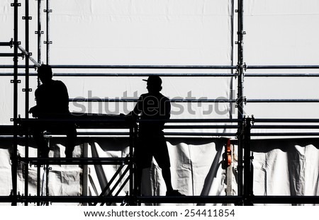 Silhouette of a workers on a construction site. - stock photo