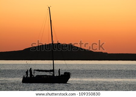 Silhouette of a yacht against a red sunset with reflecting water - stock photo