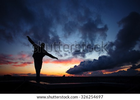 Silhouette of a young active man walking on top of the roof in the city