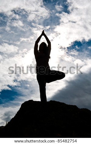 Silhouette of a young attractive girl doing yoga outside on top of a rock with sky & clouds behind her.