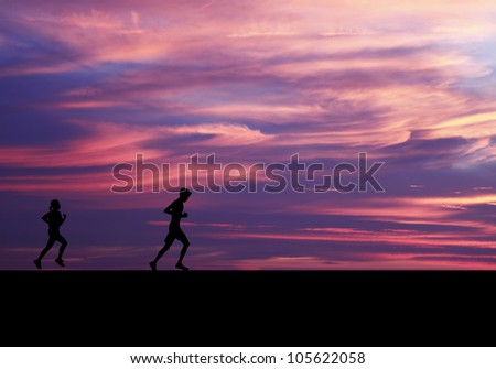 Silhouette of a young boy and girl running against a surreal evening sky with swirling candy color clouds. - stock photo