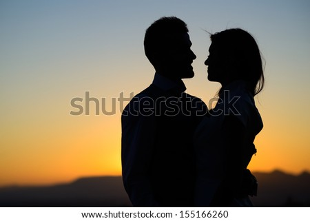 Silhouette of a young bride and groom on Sunset background  - stock photo