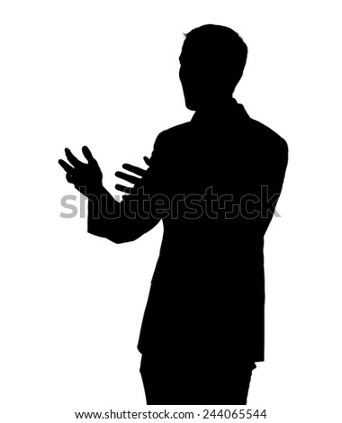 Silhouette of a young business man standing and gesturing with both hands � as if to explain, pursuade or enthusiastically tell a story.  - stock photo