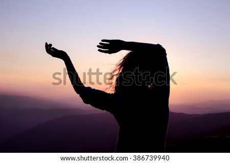 Silhouette of a young dancing woman with long wavy hair in the mountains in the backdrop of the setting sun - stock photo