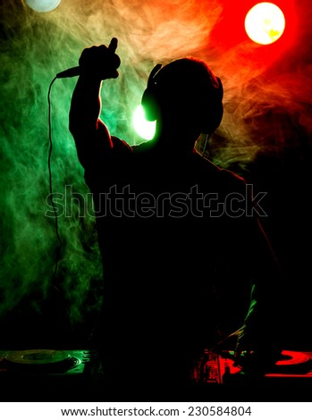 Silhouette of a young DJ at work with a microphone and the club lights on the background. - stock photo