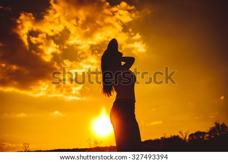 silhouette of a young girl in a vest and shorts arm straightens the hair on the background of a bright sunset