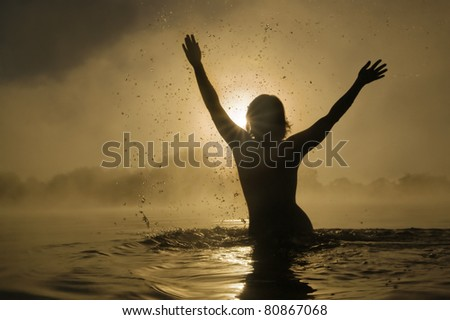 Silhouette of a young girl with raised arms in the water - stock photo