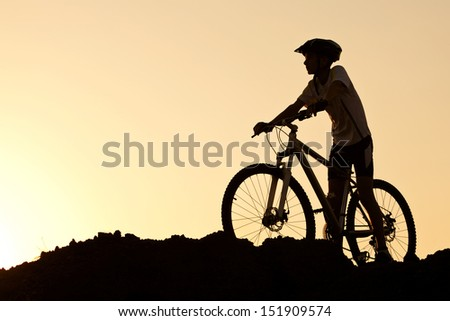 Silhouette of a young male on a mountain bike at sunset - stock photo