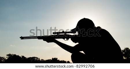 Silhouette of a young man aiming with a long rifle against setting sun