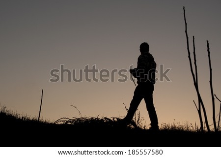 Silhouette of a young man at dusk - stock photo