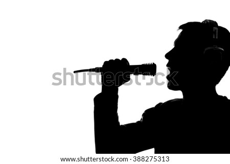 Silhouette of a young man listening to music with big headphones old