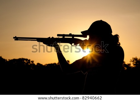 Silhouette of a young man shooting with a long rifle against sunset sky, with a sunburst