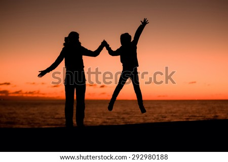 Silhouette of a young mother and her jumping son in front of a red sunset in the sky on a summer day on holidays