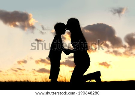 Silhouette of a young mother lovingly kissing her little child on the forehead, outside isolated in front of a sunset in the sky on a summer day. - stock photo