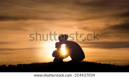 Silhouette of a young mother lovingly kissing her little child on the sunset - stock photo