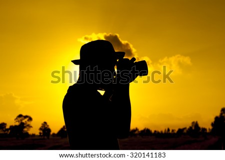 Silhouette of a young photographer during the sunset