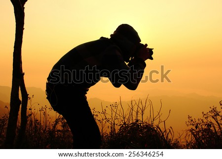 Silhouette of a young photographer during the sunset at PHU CHEEFA PARK , Chiangrai in Thailand